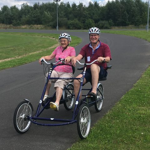 A lady and gentleman cycling together using an adapted tandem cycle