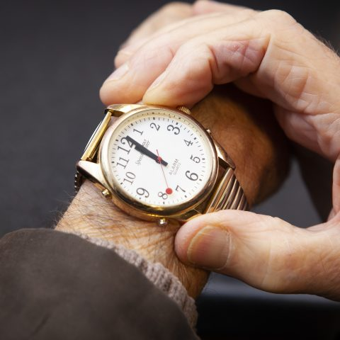 A man pressing the speech button on a talking watch