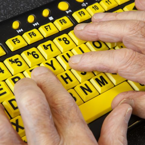 A computer keyboard with large black font on yellow keys