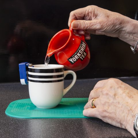 A person using a liquid level indicator to help pour water into a cup