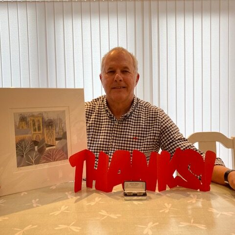 Jim Wallace with leaving gifts: a picture, cufflinks and a large card that reads 'Thanks'