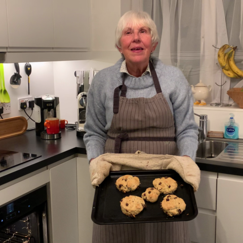 A woman standing in a kitchen, holding a tray of scones